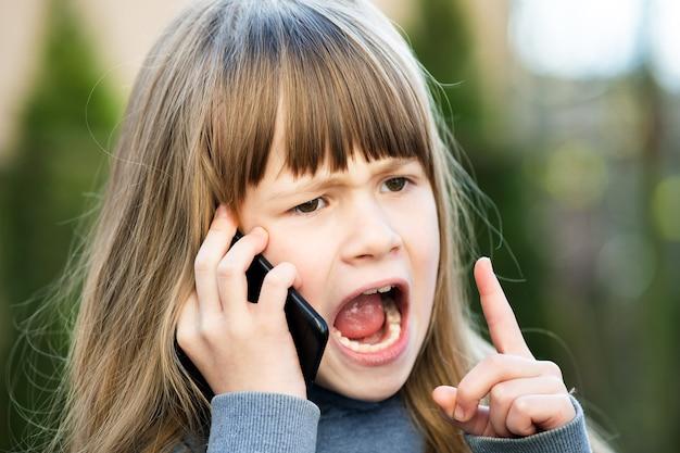 Портрет сердитой детской девочки с длинными волосами, разговаривающими по мобильному телефону.