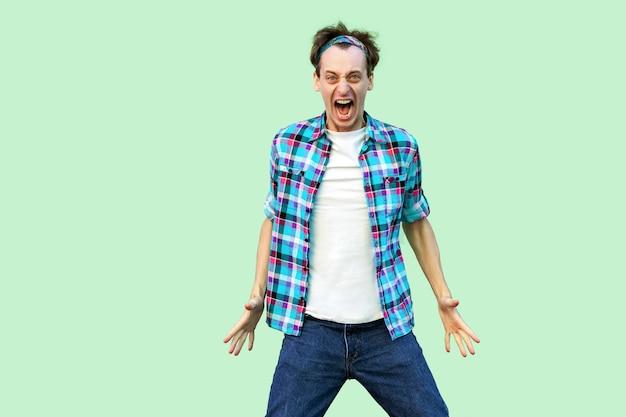 캐주얼한 파란색 체크무늬 셔츠와 머리띠를 한 화난 혼란스러운 젊은이의 초상화, 공격적인 얼굴로 카메라를 바라보고 소리를 지르고 있습니다. 밝은 녹색 배경에 고립 된 실내 스튜디오 촬영.