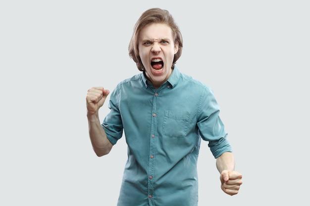 파란 캐주얼 셔츠를 입고 카메라를 쳐다보고 비명을 지르고 공격할 준비가 된 화난 미친 잘생긴 장발 금발 청년의 초상화. 밝은 회색 배경에 격리된 실내 스튜디오 촬영.