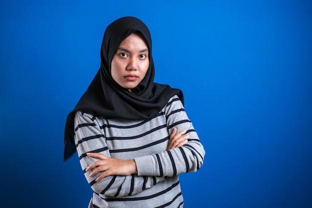 Портрет сердитой циничной азиатской мусульманской женщины с подозрительным выражением лица, смотрящей в камеру, недоверие к понятию сомнения