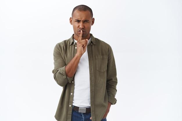 Портрет сердитого, недовольного афроамериканца, шикающего с неудовлетворенным, раздраженным лицом, тишина кладет палец на губы, хмурясь
