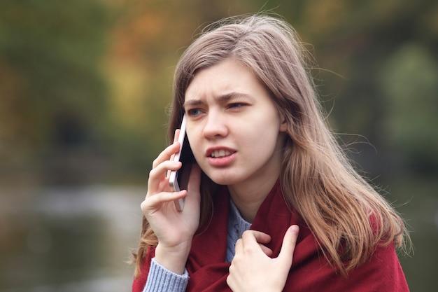 야외 공원에서 그녀의 휴대 휴대 전화에 대 한 얘기 화가 분노 좌절 된 젊은 여자의 초상화. 갈등, 스마트 폰 논쟁. 부정적인 대화.