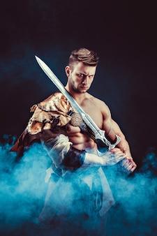Портрет разгневанного гладиатора с мечом, смотрящим против черного. изолированные