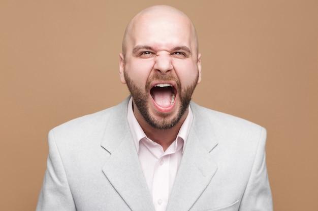 Портрет сердитого красивого лысого бородатого бизнесмена средних лет в классическом светло-сером костюме, стоящего и кричащего и смотрящего в камеру. крытая студия выстрел, изолированные на светло-коричневом фоне.