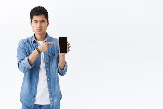 휴대폰을 가리키며 화난 판단력이 있는 아시아 남자 친구의 초상화, 실망하고 화난 설명을 기다리는 남자에게 여자친구의 문자를 보여줍니다.