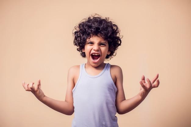 侵略を示す巻き毛を持つ怒っている子供男の子の肖像画。子供と感情の概念