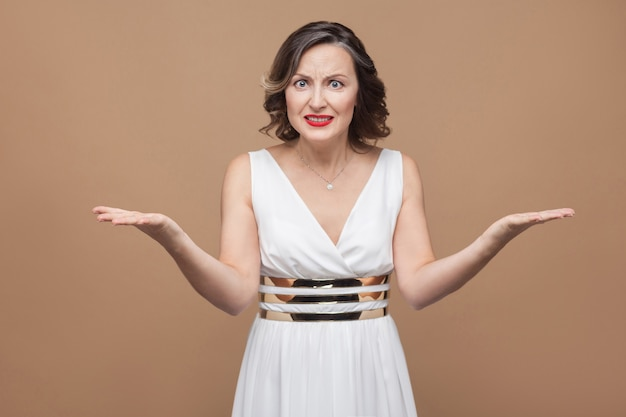 Портрет сердитой женщины босса средних лет, смотрящей на камеру. эмоционально выражающая женщина в белом платье, красных губах и темной вьющейся прическе. студийный снимок, изолированные на бежевом или светло-коричневом фоне