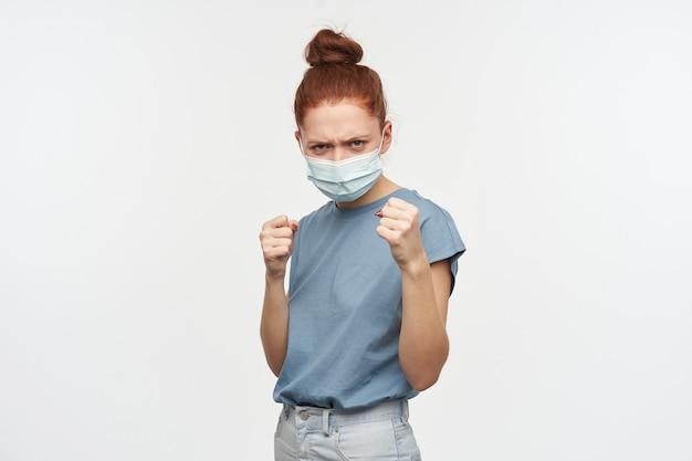 머리를 가진 성 난 빨간 머리 여자의 초상화는 롤빵에 모여. 파란색 티셔츠와 안면 보호 마스크를 착용하십시오. 주먹을 쥐고 싸울 준비를하세요. 흰 벽 위에 절연