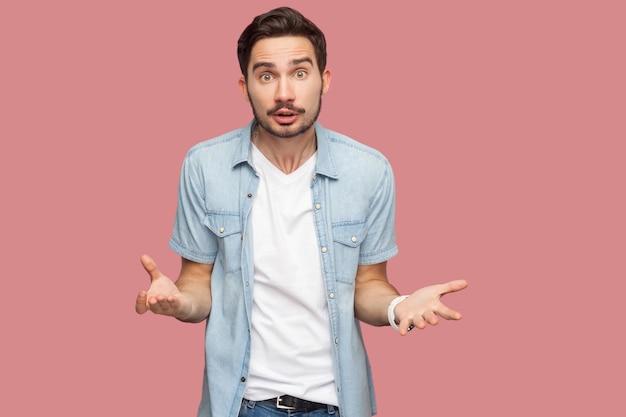 Портрет сердитого шокированного красивого бородатого молодого человека в голубой рубашке повседневного стиля, стоящего и смотрящего в камеру и спрашивающего. крытая студия выстрел, изолированные на розовом фоне.