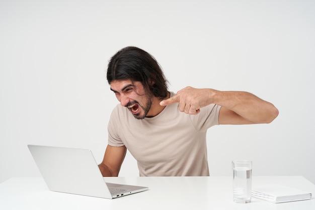 검은 머리카락과 수염을 가진 화가, 스트레스 사업가의 초상화. 사무실 개념. 노트북에서 작업. 노트북에 소리를 지르고 손가락을 가리 킵니다. 흰 벽 위에 절연 직장에 앉아