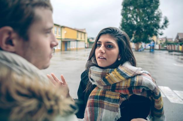 Портрет сердитой женщины, спорящей с молодым человеком во время жесткой ссоры на открытом воздухе. пара отношений и концепции проблем.
