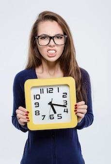 Портрет злой женщины, держащей настенные часы, изолированные на белом фоне