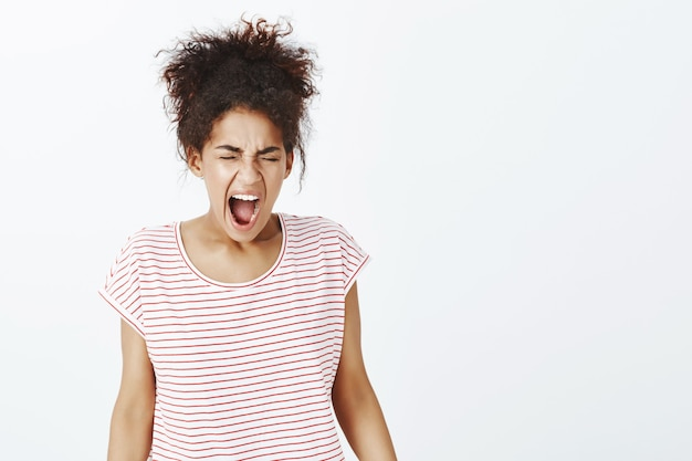 スタジオでポーズをとってアフロの髪型を持つ怒っている女性の肖像画