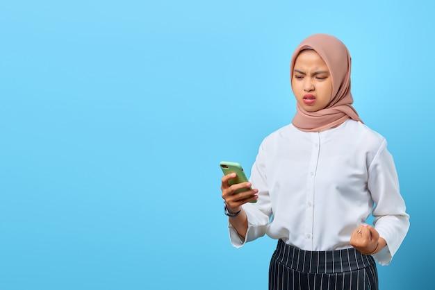 Портрет сердитой молодой азиатской женщины, смотрящей на мобильный телефон, потому что получает плохие новости