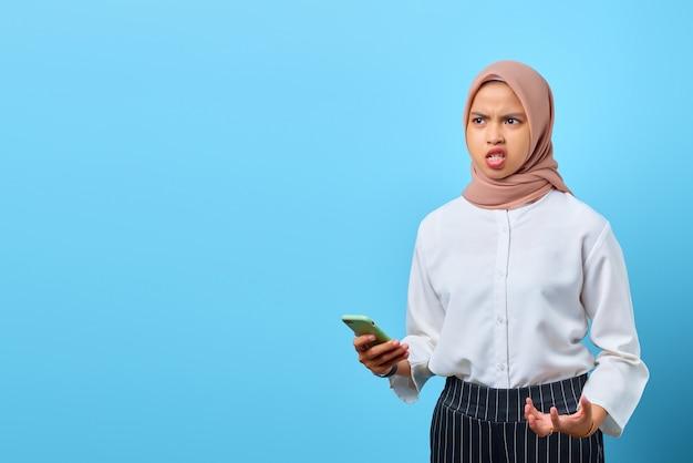 Портрет сердитой молодой азиатской женщины, использующей мобильный телефон и смотрящей в сторону