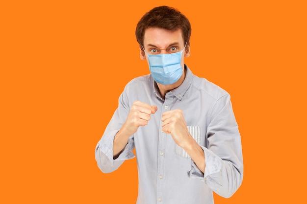 ボクシングの拳に立ってカメラを見て、ウイルスに対して攻撃する準備ができているサージカルマスクを持つ怒っている若い労働者の男の肖像画。オレンジ色の背景に分離された屋内スタジオショット。