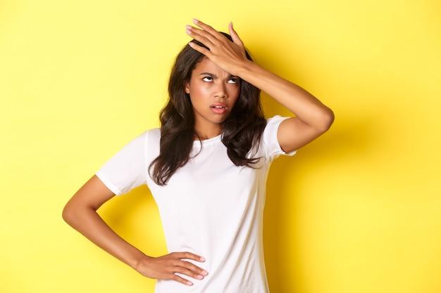 Портрет раздраженной афро-американской девушки, хлопнувшей по лбу и закатившей глаза, надоело, забыл что-то важное, стоя на желтом фоне.