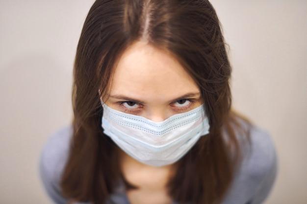 Портрет раздраженной девушки в защитной медицинской маске, недоверчиво смотрящей