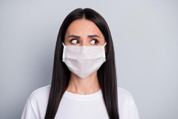 不安な落ち込んでいる女の子の肖像画は、covid19がパンデミックの外観を広めることへの恐怖を感じます灰色の背景の上に分離された医療マスク白いtシャツを着用してください