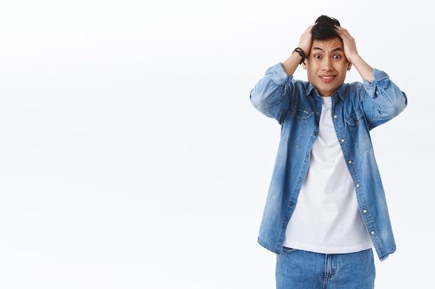 당황하고 당황한 아시아 남성의 초상화는 공황 상태에 머리를 잡고, 좌절하고 긴장하며, 큰 문제가 있고, 걱정스러운 흰 벽에 서 있습니다.