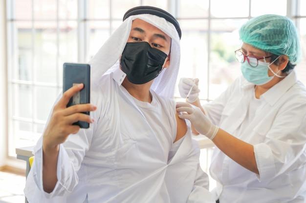 免疫を得るためにcovidワクチンを取得した後の電話でのアラブのイスラム教徒の男性の自分撮りの肖像画