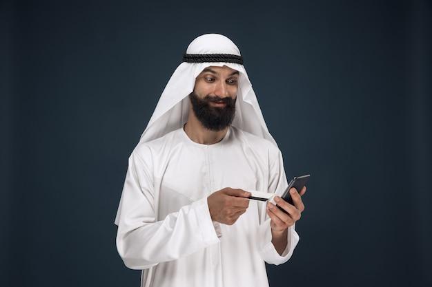 アラビアのサウジアラビアの実業家の肖像画。請求書の支払い、オンラインショッピング、または賭けにスマートフォンを使用している男性。ビジネス、金融、顔の表情、人間の感情の概念。