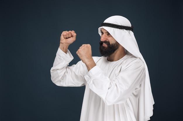 紺色の空間にアラビアのサウジアラビアの実業家の肖像画。立って、笑顔で祝う若い男性モデル
