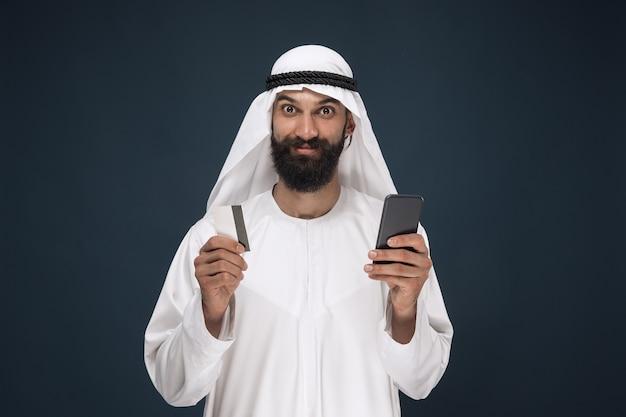ダークブルーのスタジオの背景にアラビアのサウジアラビアの実業家の肖像画。請求書の支払い、オンラインショッピング、または賭けにスマートフォンを使用している男性。ビジネス、金融、顔の表情、人間の感情の概念。