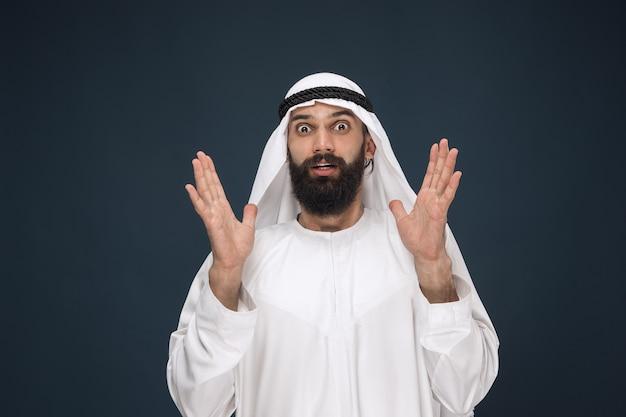 ダークブルーのスタジオの背景にアラビアのサウジアラビアの実業家の肖像画。ショックを受けて驚いて立っている若い男性モデル。ビジネス、金融、顔の表情、人間の感情の概念。