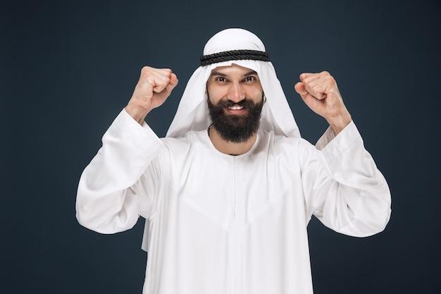 진한 파란색 스튜디오 배경에 아라비아 사우디 사업가의 초상화. 젊은 남성 모델 서, 웃고 축하. 비즈니스, 금융, 표정, 인간 감정의 개념.