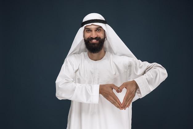 アラビアのサウジアラビアの実業家の肖像画。心のジェスチャーを示す立っている若い男性モデル。ビジネス、金融、顔の表情、人間の感情の概念。