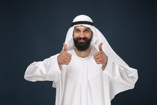 アラビアのサウジアラビアの実業家の肖像画。親指を立てるジェスチャーを示す立っている若い男性モデル。ビジネス、金融、顔の表情、人間の感情の概念。