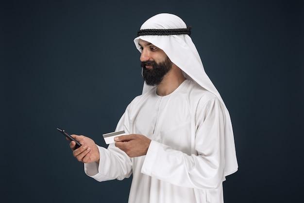 アラビアのサウジアラビアのシェイクの肖像画。請求書の支払い、オンラインショッピング、または賭けにスマートフォンを使用している男性。