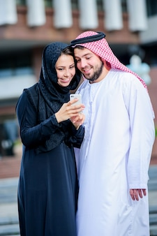 アラビアの服を着た陽のカップルの肖像画は携帯電話で遊ぶ。