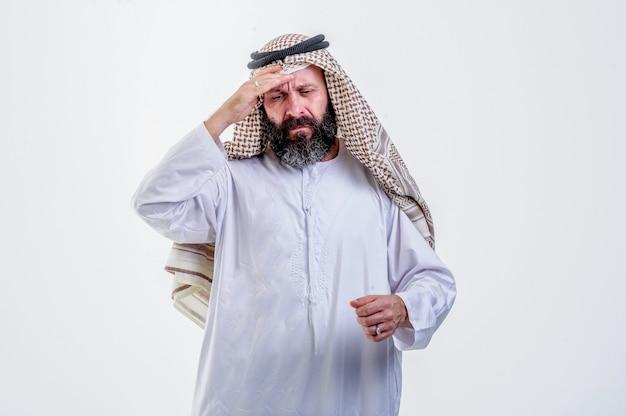 아랍어 남자 남자의 초상화는 흰색 배경에 고립 된 손바닥으로 이마를 만지고 눈을 유지하는 고온 신체 압력을 갖는 나쁜 느낌의 초상화