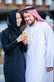 携帯電話で遊ぶアラビアの若いカップルの肖像画
