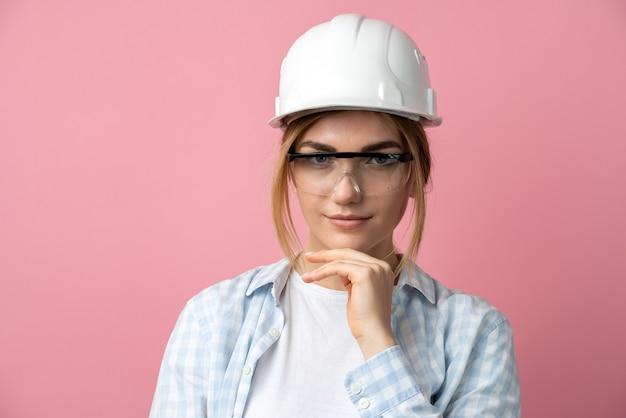 ピンクの背景のスタジオでヘルメットの建築家金髪学生の肖像画