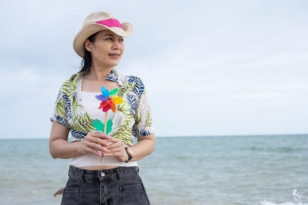 화려한 풍력 터빈이나 바람 장난감을 가지고 해변에 있는 아시아 여성의 초상화