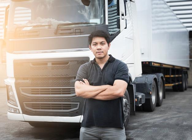 세미 트레일러 트럭으로 팔짱을 끼고 서 있는 아시아 트럭 운전사의 초상화