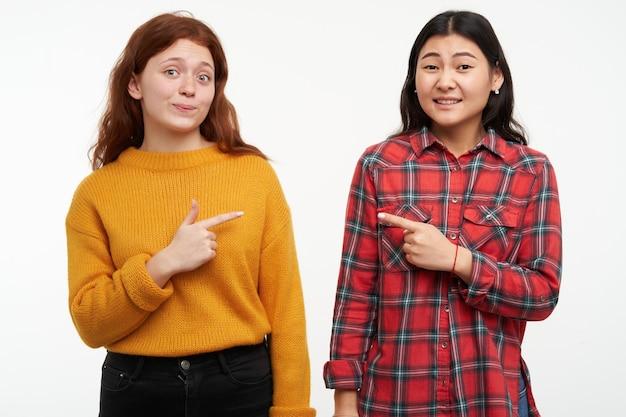 アジア人と白人の女の子の肖像画。流行に敏感な友達が指差して、お互いを責めます。黄色いセーターと市松模様のシャツを着ています。人々の概念。白い壁に隔離