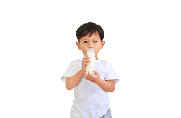 白い背景で隔離のガラス瓶から牛乳を飲むアジアの男の子の肖像画。
