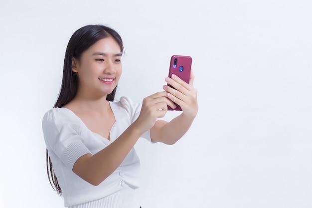 白いシャツに黒い長い髪を持っているアジアの美しい少女の肖像画は、彼女の手でスマートフォンを持って笑っています。彼女は白い背景で自分撮り写真を撮ります。