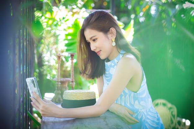 アジアの美しい女性の肖像画長い茶色の髪は彼女の手でスマートフォンを保持し、リラックスした気分になります