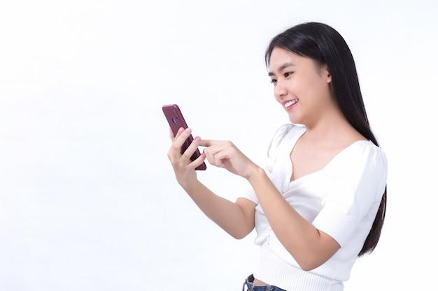 アジアの美しい女性の肖像画白い背景の上で楽しく携帯電話を使用してください。
