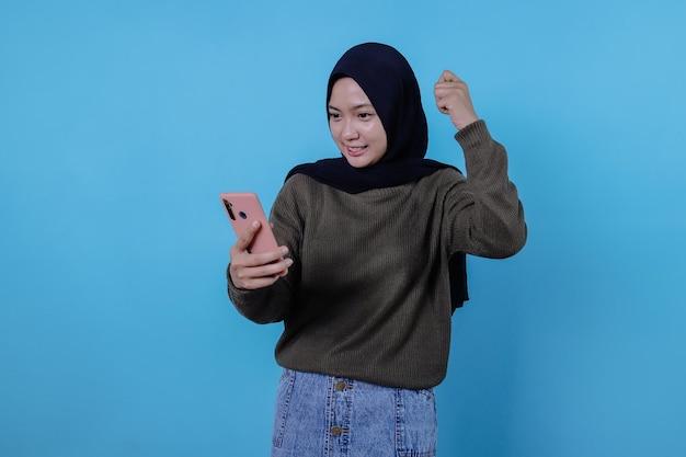 히잡을 쓴 아름다운 아시아 여성의 초상화는 휴대전화로 마사지를 읽고 재미있고 웃고 있다