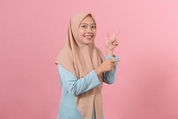 Портрет азиатской красивой молодой мусульманской женщины, указывающей обеими руками пальцем на верхней стороне с улыбающимся лицом, изолированным на розовом фоне