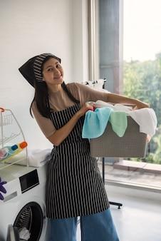 아시아의 아름다운 젊은 여성의 초상화는 세탁 기계에서 씻기 위해 다채로운 수건으로 세탁 바구니를 들고 있습니다. 주말에 집에서 집안일.