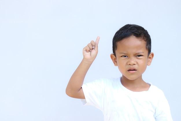 何かを指しているアジアの少年の肖像画。製品のプレゼンテーション、広告などのためのコピースペース付き