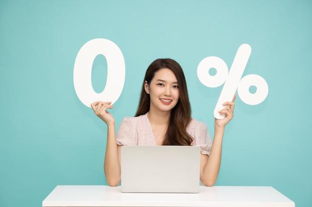 Портрет азиатской деловой женщины, показывающей и удерживающей 0 чисел или ноль процентов, изолированные на светло-зеленом фоне