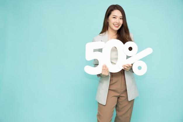 Портрет азиатской деловой женщины, показывающей и держащей 50 номеров или пятьдесят процентов, изолированных на светло-зеленом фоне